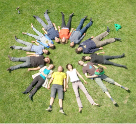 Menschen liegen in einem Kreis auf einer Wiese