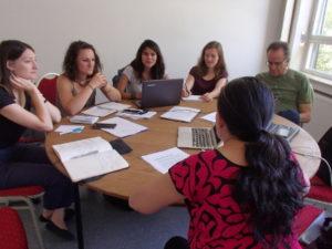 Sechs Personen sitzen an einem runden Tisch und diskutieren.