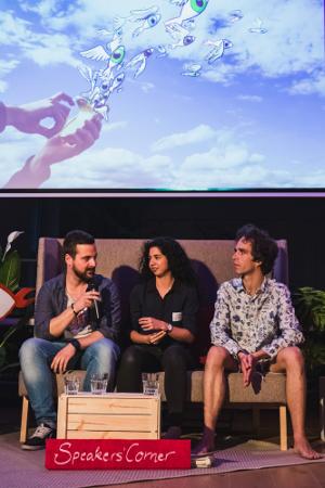 Drei Personen sitzen auf einer kleinen Bühne und führen ein Gespräch.