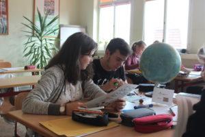 Zwei Schüler sitzen an einem Tisch und arbeiten fleißig.