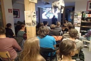 Auf dem Foto ist eine Gruppe von Leuten zu sehen, die sich einen Vortrag anhört.