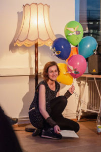 Eine Frau hält 6 bunte Luftballons in der Hand.