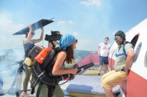 Ein Schauspieler wird beim Dreh am Flugzeugnotausgang mit einem Laubbläser benebelt.